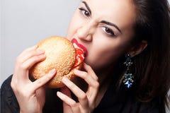 Девушка есть большой гамбургер, фото студии Стоковое Изображение