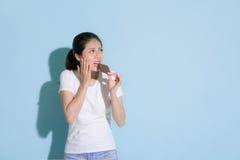 Девушка есть еду шоколада смотря пустую область Стоковые Фотографии RF