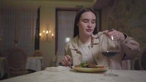 Девушка есть красиво служила лапши аппетита с arugula выпивая красное вино и улыбку к кто-то сток-видео