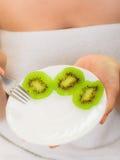 Девушка есть куски плодоовощ кивиа диетпитание здоровое Стоковое Фото