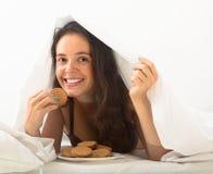 Девушка есть печенья в кровати стоковые фотографии rf