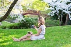 Девушка есть суши в саде вишневого цвета стоковые изображения rf