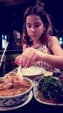 Девушка есть тайскую еду стоковое изображение rf