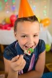 Девушка есть торт во время вечеринки по случаю дня рождения дома Стоковая Фотография