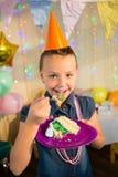Девушка есть торт во время вечеринки по случаю дня рождения дома Стоковое Изображение RF