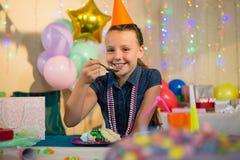 Девушка есть торт во время вечеринки по случаю дня рождения дома Стоковые Изображения