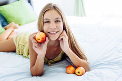 Девушка есть яблоко и ослабляя в спальне Стоковое Изображение