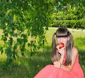Девушка есть яблоко outdoors Стоковая Фотография