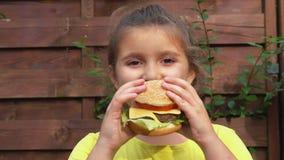 Девушка ест большой бургер с сыром акции видеоматериалы