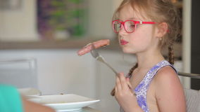Девушка ест сосиску на вилке сток-видео