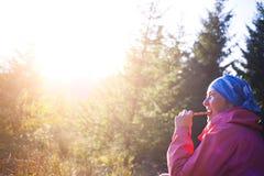 Девушка ест фаст-фуд в природе Стоковая Фотография