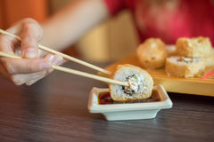 Девушка ест японскую еду держит крены суш с деревянными палочками и moka они в соевом соусе Стоковые Изображения