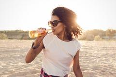 Девушка детенышей довольно африканская в солнечных очках выпивая пиво Стоковые Фотографии RF