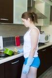 Девушка детенышей расстроенная с перчатками приближает к раковине Стоковое Изображение RF