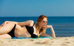 Девушка летних каникулов в бикини загорая на пляже Стоковое фото RF