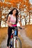 Девушка ехать велосипед на дороге леса, усмехаясь в хорошем настроении в spo стоковые фото