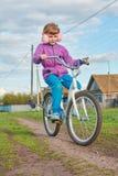Девушка ехать велосипед в деревне Стоковое Изображение RF