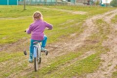 Девушка ехать велосипед в деревне Стоковые Фотографии RF