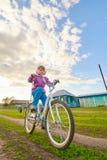 Девушка ехать велосипед в деревне Стоковая Фотография