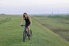 Девушка ехать горный велосипед на дороге асфальта, красивый портрет велосипедиста стоковое фото