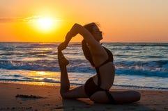 Девушка делает йогу, сидя в Одн-шагающем представлении короля Голубя, Eka Pada Rajakapotasana на пляже с первым солнечным лучом Стоковые Изображения RF