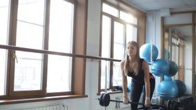 Девушка делает deadlift с прямыми ногами и штангой сток-видео