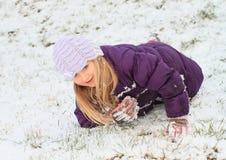 Девушка делая ангела в снеге Стоковые Фото