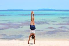Девушка делая гимнастику на тропическом пляже лагуны Стоковое Изображение RF