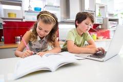 Девушка делая ее домашнюю работу пока мальчик используя компьтер-книжку в кухне Стоковое Изображение