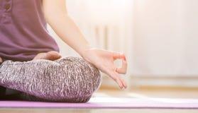 Девушка делая йогу внутри помещения в asana лотоса стоковая фотография