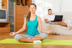 Девушка делая йогу и человек с компьтер-книжкой Стоковые Изображения RF