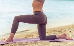 Девушка делая йогу на пляже Стоковое Фото