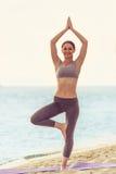 Девушка делая йогу на пляже Стоковые Фотографии RF