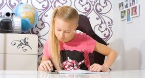Девушка делая домашнюю работу используя калькулятор smartphone Стоковое Фото