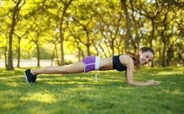 Девушка делая представление планки локтя outdoors Стоковое Фото