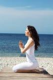 Девушка делая тренировки йоги на морском побережье Стоковое Изображение RF