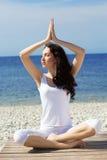 Девушка делая тренировки йоги на морском побережье Стоковое Изображение