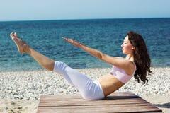 Девушка делая тренировки йоги на морском побережье Стоковые Изображения