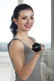 Девушка делая тренировку используя гантели для бицепсов Стоковые Фото