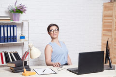 Девушка дела сидит на компьютере в папках бумаги офиса Стоковая Фотография RF