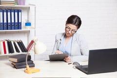 Девушка дела сидит на компьютере в папках бумаги офиса Стоковые Изображения RF