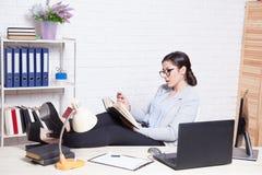 Девушка дела сидит на компьютере в папках бумаги офиса Стоковые Фотографии RF