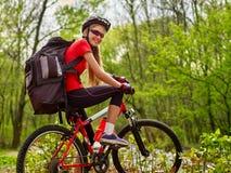 Девушка едет велосипед на зеленой траве в парке внешнем Стоковое Изображение