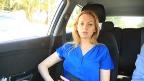 Девушка едет в автомобиле рядом с водителем и унылыми взглядами вне окно акции видеоматериалы