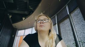 Девушка ждет ваш заказ сидя на таблице в кафе сток-видео