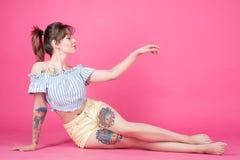 Девушка, женщина с татуировкой на розовой предпосылке, стиле Pin поднимающем вверх Стоковые Изображения