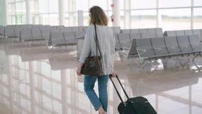 Девушка женщины волос имбиря красная идя с сумкой чемодана багажа завальцовки