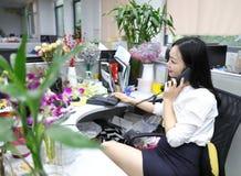 Девушка женщины дамы офиса Азии китайская на стуле делает настольный телефонный аппарат пользы звонка побеседовать рабочее место  Стоковое Изображение