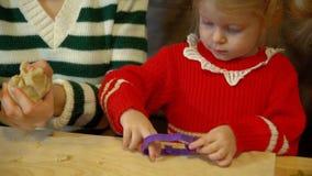 Девушка женщины и малыша подготавливая пряник для обедающего Рожденственской ночи семьи акции видеоматериалы
