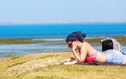 Девушка женщины лежа на книге чтения травы стоковое изображение